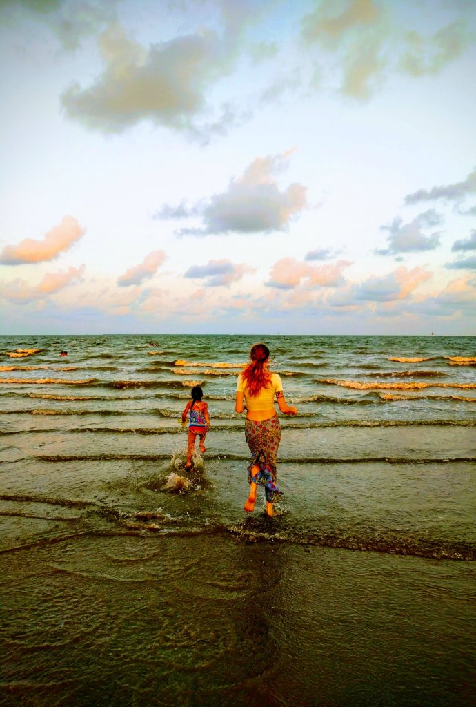 A young girl and a woman run through the waves into the water, with sunset behind them